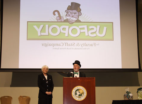 The host of USF-opoly speaks at a dais